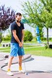 Человек играя миниатюрный гольф Стоковая Фотография