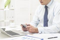 Человек играя на его сотовом телефоне на работе Стоковое фото RF