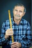 Человек играя на каннелюре трубы стоковая фотография