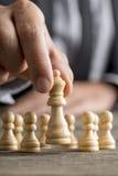 Человек играя шахмат двигая часть ферзя Стоковая Фотография