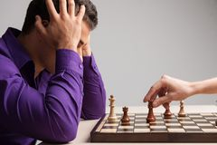 Человек играя шахмат на белой предпосылке Стоковые Фото