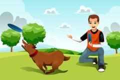 Человек играя frisbee с его собакой Стоковое Изображение