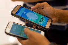 Человек играя pokemon идет на множественные телефоны стоковое изображение