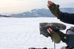 Человек извлекая снег от его ботинка зимы Стоковое фото RF