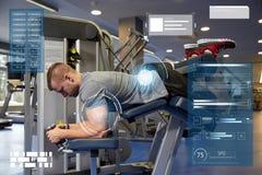 Человек изгибая мышцы ноги на машине спортзала Стоковые Фотографии RF