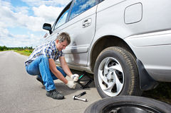 Человек изменяя запасную автошину автомобиля Стоковая Фотография RF