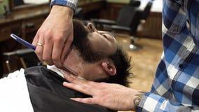 Человек имея бритье на конце парикмахерской вверх Профессиональный парикмахер используя прямую бритву с острым гелем лезвия и сли видеоматериал