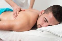 Человек имея задний массаж в спа-центре Стоковые Изображения RF