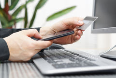 Человек использует кредитную карточку и мобильный телефон для на линии оплаты