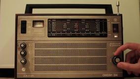 Человек использует старое радио, ища радиоволны акции видеоматериалы