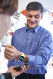 Человек используя безконтактную оплату App на умном вахте в магазине Стоковое Фото