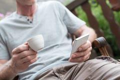 Человек используя его smartphone и держащ чашку кофе Стоковое Фото