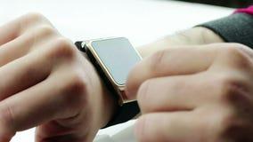 Человек используя его smartwatch app на белой предпосылке акции видеоматериалы