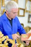 Человек используя листовое золото для того чтобы восстановить объект стоковая фотография