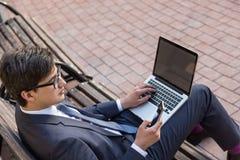 Человек используя компьтер-книжку и smartphone Стоковое Изображение