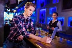 Человек используя компьтер-книжку на счетчике бара с деятельностью бармена Стоковое Изображение