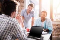 Человек используя компьтер-книжку пока коллеги обсуждая проект, концепцию делового совещания мелкого бизнеса Стоковая Фотография