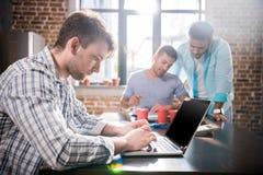 Человек используя компьтер-книжку пока коллеги обсуждая проект, концепцию делового совещания мелкого бизнеса Стоковое Фото