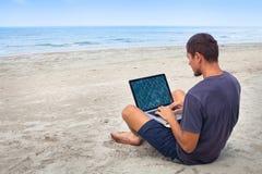 Человек используя компьютер на пляже стоковое фото
