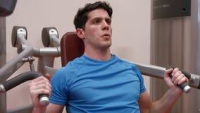 Человек используя машину весов в спортзале акции видеоматериалы