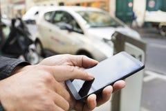 Человек используя мобильный телефон перед станцией Autolib, Парижем Стоковое Фото