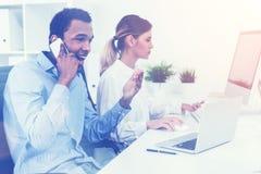 Человек используя мобильный телефон пока женщина работая его тонизированной стороной, стоковая фотография rf