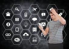 Человек используя мобильный телефон против значков применения на черной предпосылке Стоковое Фото