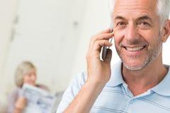 Человек используя мобильный телефон с газетой чтения женщины дома Стоковое Изображение