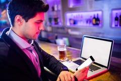 Человек используя мобильный телефон с стеклом пива и компьтер-книжки на таблице на счетчике бара Стоковое Изображение