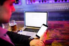 Человек используя мобильный телефон с стеклом пива и компьтер-книжки на таблице на счетчике бара Стоковое Фото
