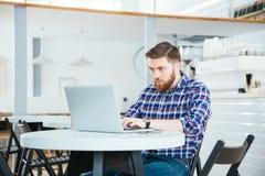 Человек используя портативный компьютер в кафе Стоковое Изображение RF