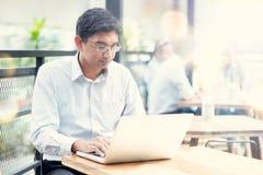 Человек используя портативный компьютер на внешнем кафе Стоковые Фото