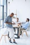 Человек используя таблетку пока коллеги обсуждая стратегию на рабочем месте в офисе Стоковое Фото
