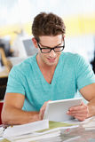 Человек используя таблетку цифров в многодельном творческом офисе Стоковые Изображения RF