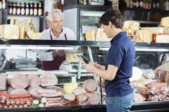 Человек используя таблетку цифров пока сыр упаковки продавца Стоковое фото RF