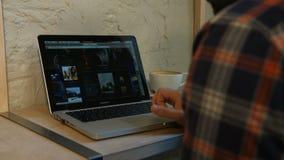 Человек используя тетрадь и выпивающ кофе в кафе акции видеоматериалы
