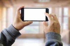 Человек используя умный телефон на окне с предпосылкой здания города Стоковое фото RF