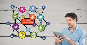 Человек используя цифровую таблетку против социальных значков средств массовой информации в предпосылке Стоковое фото RF