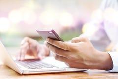 Человек используя smartphone и компьютер Стоковое Изображение