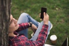 Человек используя smartphone и полагающся к стволу дерева на парке Стоковые Фото
