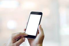 Человек используя smartphone на предпосылке нерезкости Стоковые Фото