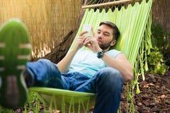 Человек используя smartphone на hammok стоковые фото