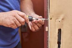 Человек исправляя замок в старой двери Стоковое Изображение RF