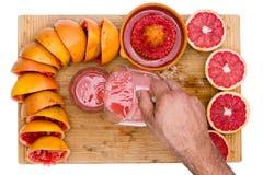 Человек лить свеже сжиманный рубиновый сок грейпфрута Стоковая Фотография