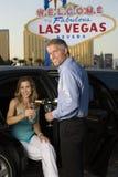 Человек лить Шампань в стекле женщины сидя в лимузине Стоковое Изображение RF