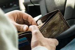 Человек ища деньги в его бумажнике Стоковое Фото