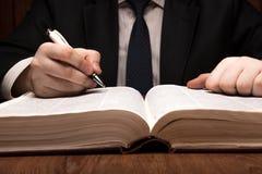 Человек ищет информация в словаре стоковая фотография