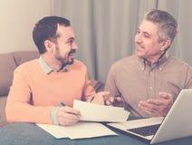 Человек и администраторов по сбыту обсуждают контракт стоковое фото