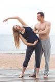 Человек и беременная женщина делают йогу на пляже Стоковые Фотографии RF