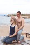 Человек и беременная женщина делают йогу на пляже Стоковая Фотография RF